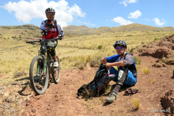One person sitting on a mountain bike and another sitting on the ground on a golden grassy hillside