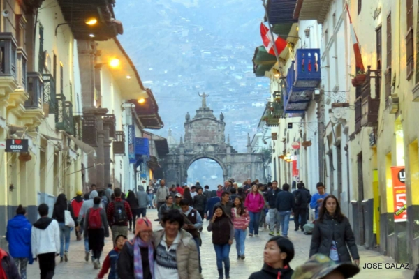 Many people walking on the wide cobblestoned street in the plaza in Cusco Peru, surrounded by pale yellow buildings