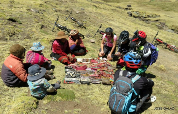4 people in bike helmets sitting on ground next to a colorful blanket across from a Peruvian woman and her family sitting on the ground