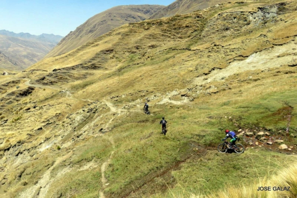 Distant view of three mountain bikers cutting across a grassy mountainside on narrow trails