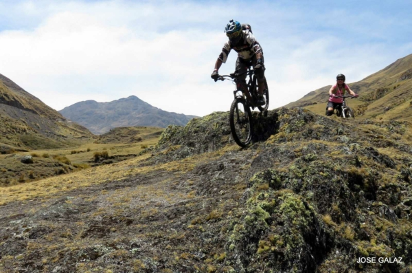 Mountain Biker riding over moss-covered rocks in mountain valley in Peru