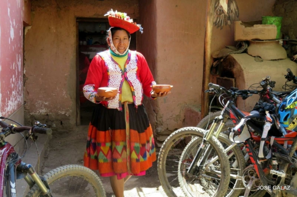 Woman in traditional Peruvian clothing of red dress and red hat, carrying two small orange bowls of food past a couple of mountain bikes parked outside a small house