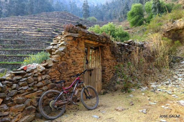 A red bike leaning against remains of a stone wall with a wooden door in front of  wide stone steps going up mountainside in Ollantaytambo