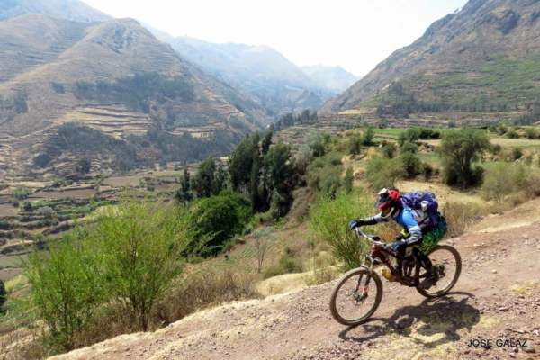 Mountain biker riding quickly down gravel trail with Peruvian mountains and green valley in background