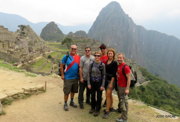 6 People from mountain bike tour posing together  on lookout point over Macchu Picchu