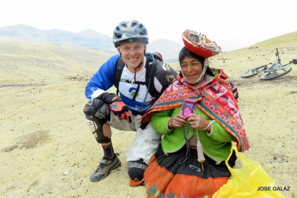 Man in mountain bike gear kneeling next to Peruvian woman wearing brightly colored clothing selling souvenirs