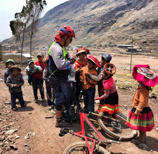 Mountain Biker standing next to his bike lying on the ground as he hands out small toys to group of young Peruvian children