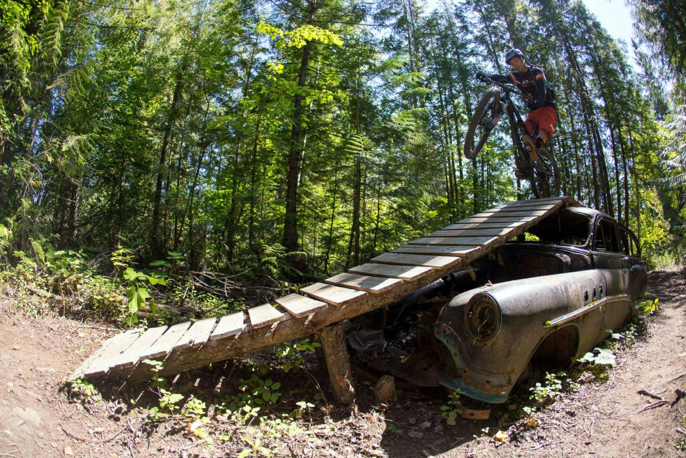 Person on mountain bike with front wheel popped up, ready to ride down wood slat ramp placed over the rusted out body of a car