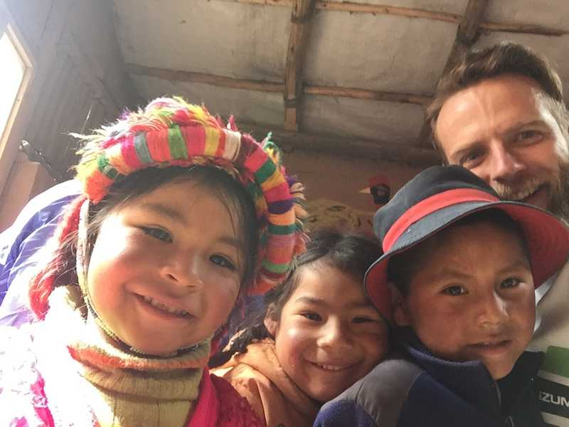 Three Peruvian children and one white man smiling as they look at the camera