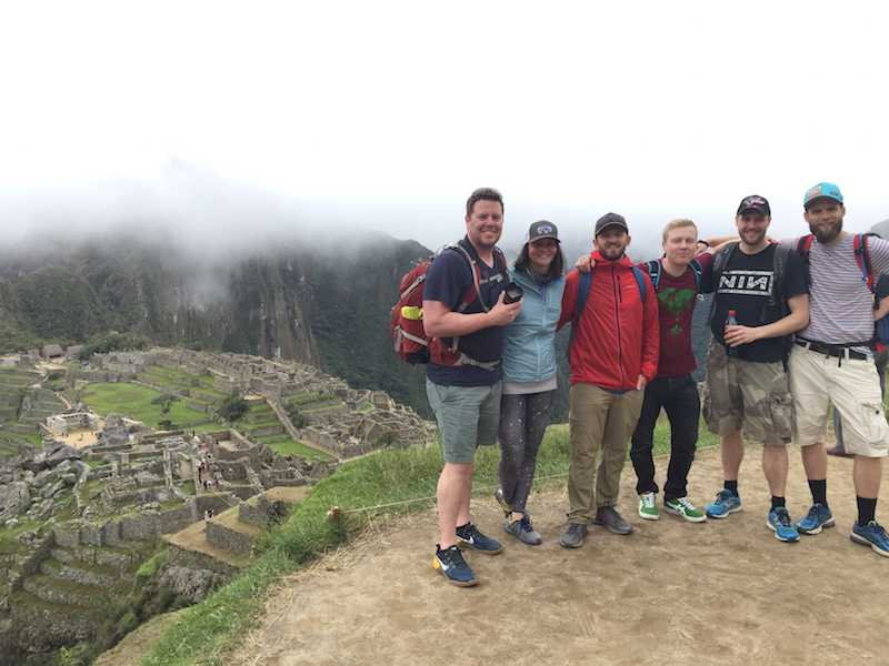 6 people standing side by side on a hilltop overlooking Macchu Picchu