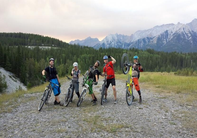 5 men posing with their bikes in the mountains