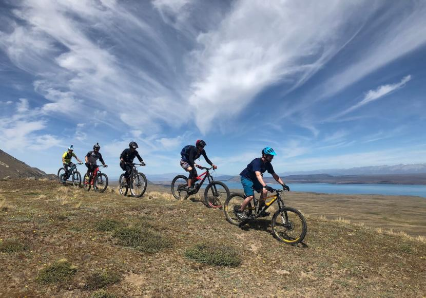 5 Mountain Bike Riders riding in a line, on trail under a blue sky