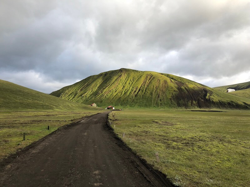 Small road cutting down center of photo, surrounded by mossy green Icelandic landscape and leading to a green hill in the distance