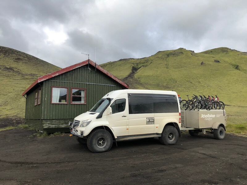 Trailer full of mountain bikes hitched to a white van, parked in front of a small house structure in Iceland