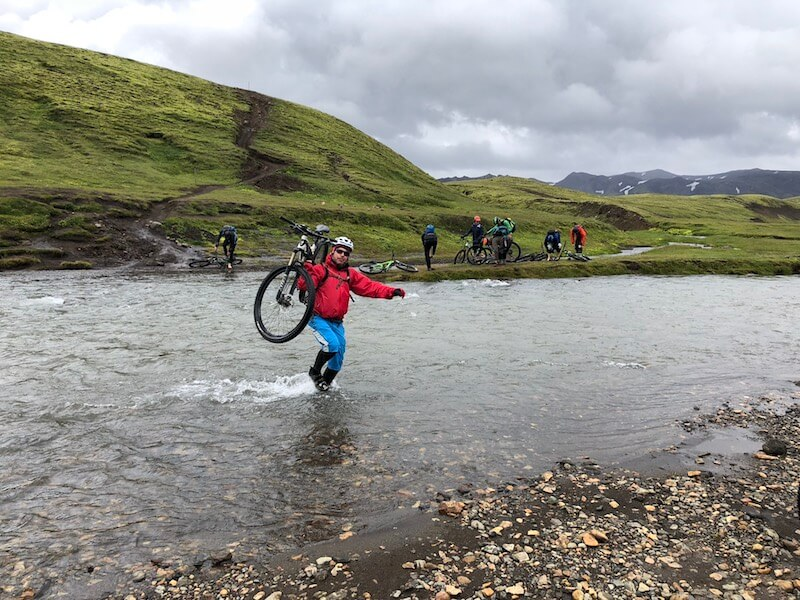 Mountain Biker carrying his bike across a shallow body of water with green and mossy Icelandic hills in background
