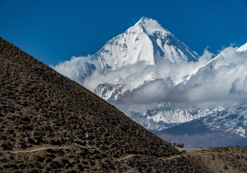 Seen during the bike tour in Nepal, the slope of a mountain in Nepal cutting diagonally across bottom half of image with blue sky behind it.