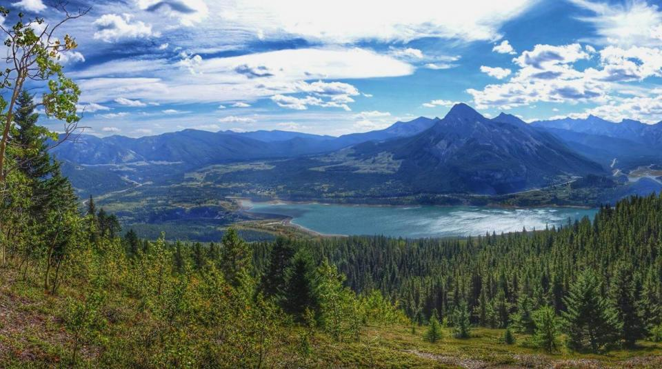 Wide, up-high view of landscape with greenery and trees in foreground, lake in middle, and mountains in the background