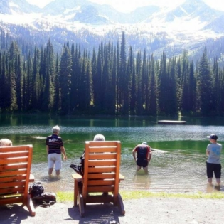 View from back of two people sitting in wood beach-style chairs watching three people stand in mountain lake with their pant-legs rolled up