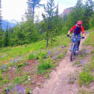 Person on mountain bike riding towards camera on a dirt path, surrounded by grass and mountain greenery