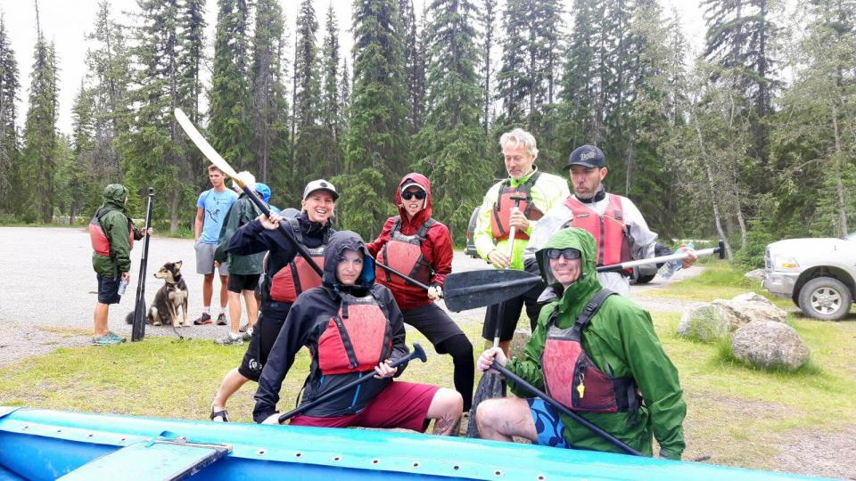 6 people in white water rafting gear posing with paddles with blue raft visible in foreground