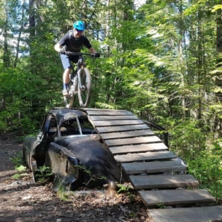 Man on mountain bike on trail in woods coming down wood slat ramp that goes from on top of a busted up car to the ground