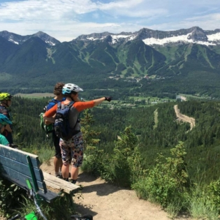 4 people in mountain bike gear standing on trail overlooking mountain valley. One sits on a bench and another is pointing while two other look