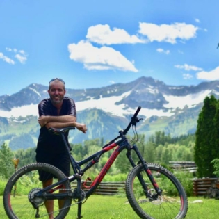 Man smiling with bike in front of him, leaning on bike seat and mountains in background