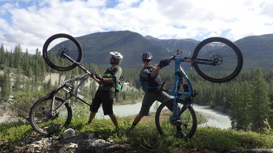 2 people posing in mountain landscape with their backs to each other and holding their bikes upright on back wheel