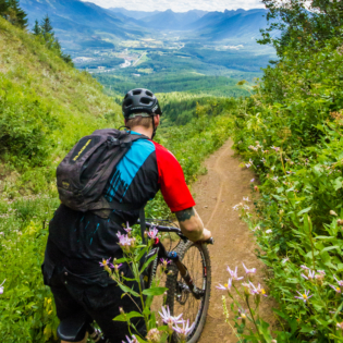 View from back of man on mountain bike on dirt trail with steep, grass-covered inclines on left and right and mountain valley ahead of him