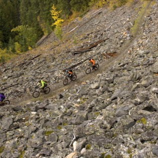 Bird's eye view of 4 mountain bikers on mountain trail surrounded by rocks with sharp decline and trees on their right