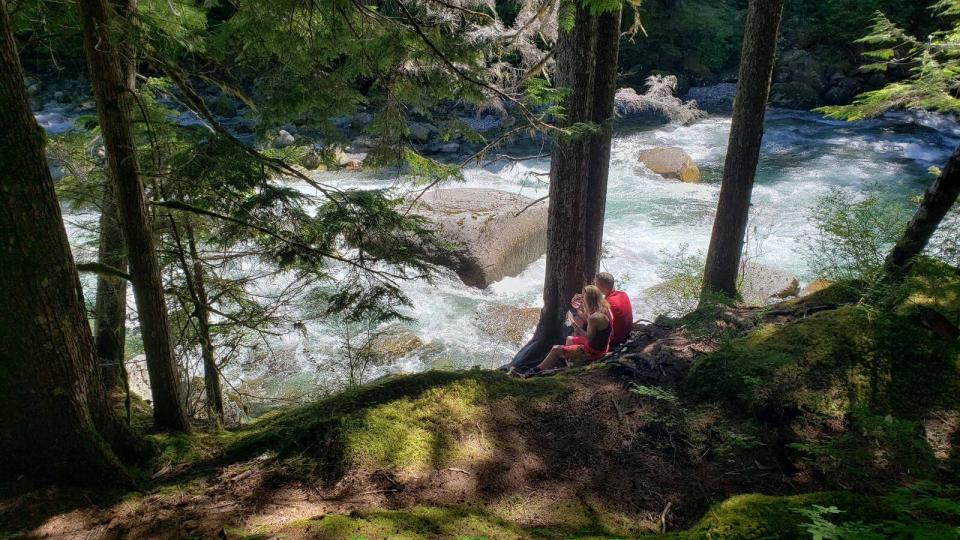 Mountain bikers riding trail above small river bank