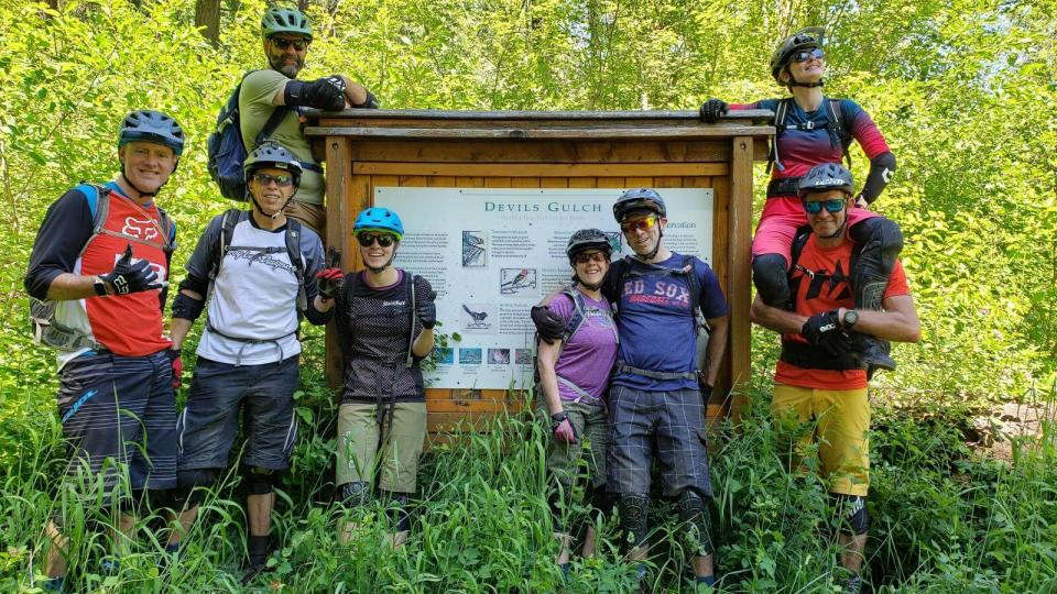 6 people in mountain bike gear posing in front of large wooden info sign in forest