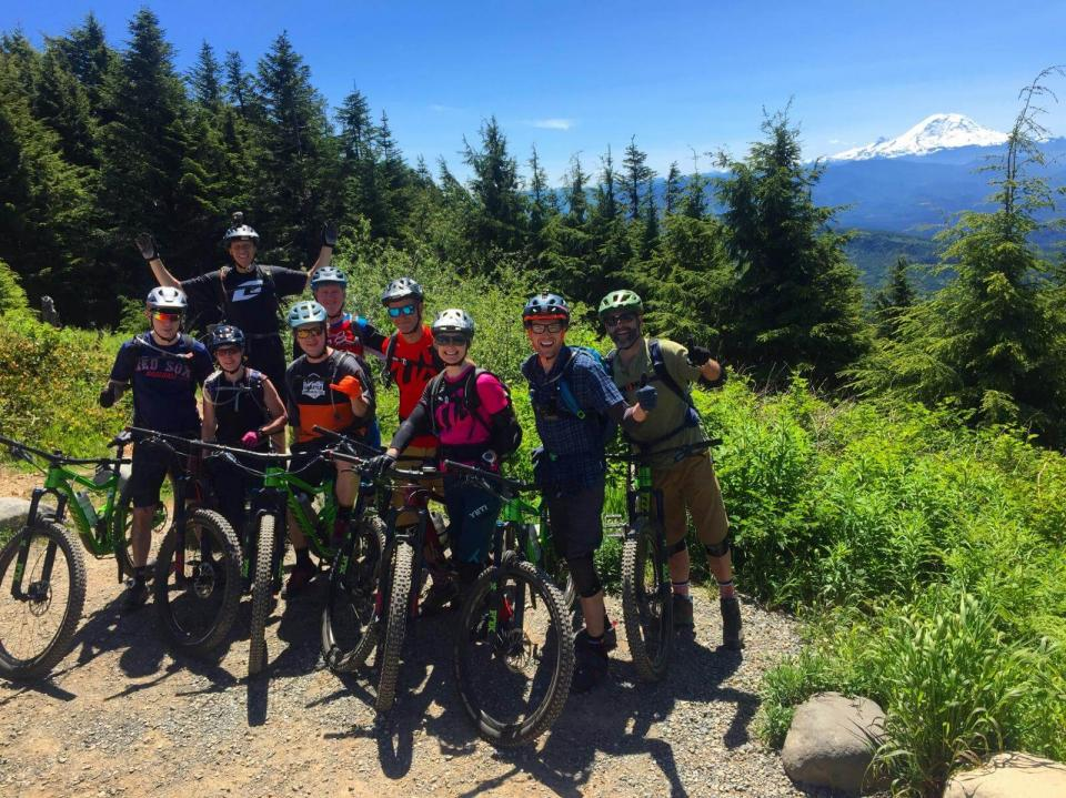 Group of mountain bikers in Seattle posing with their bikes on a grassy mountain field