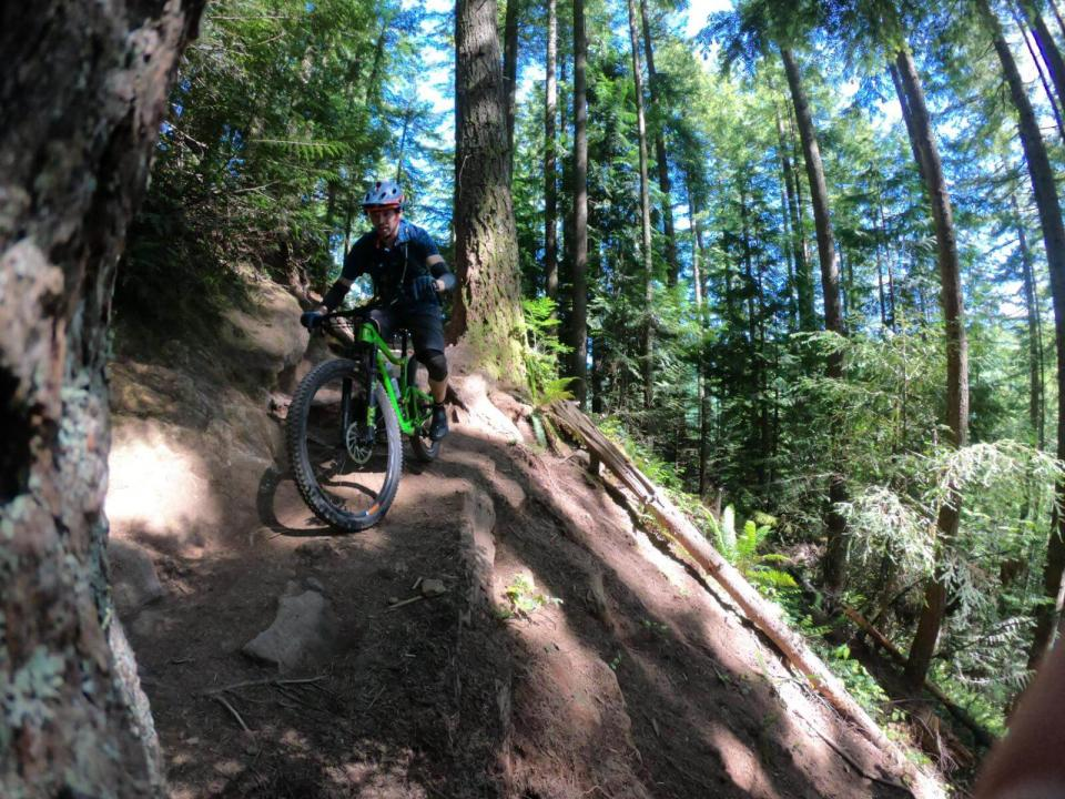 Mountain biker on dirt trail with steep drop on right, surrounded by trees