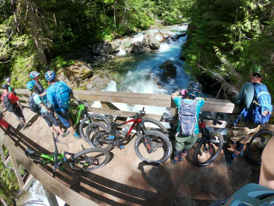 View from above of mountain bikers walking their bikes across a small wooden footbridge above small river
