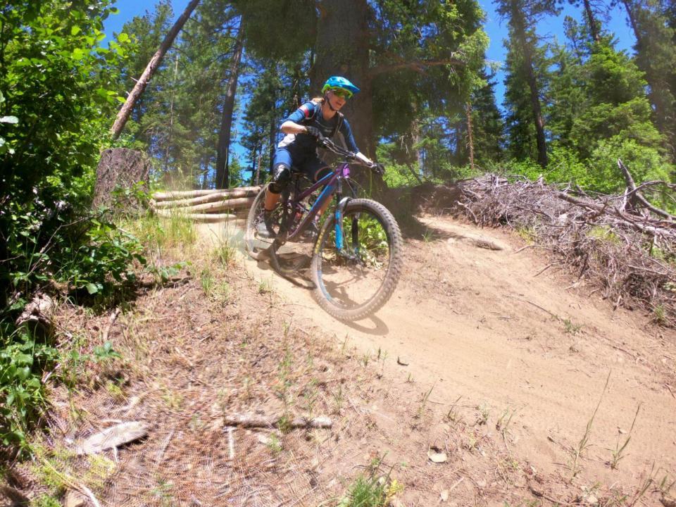 Mountain biker going down slight decline on dirt path