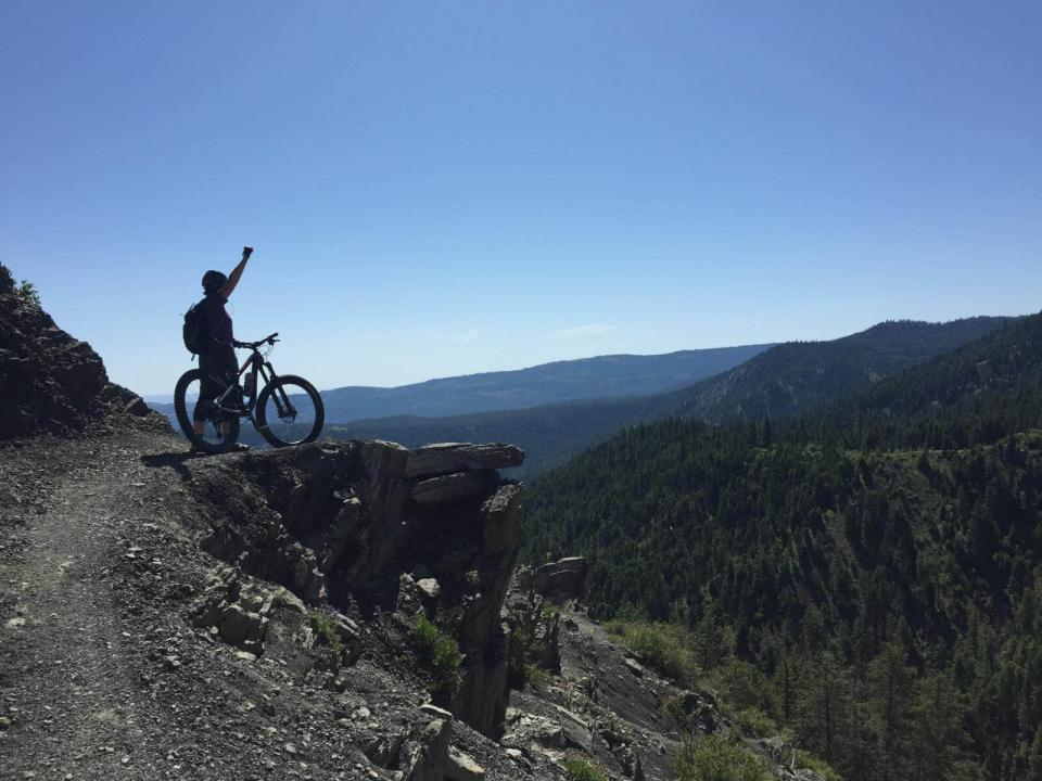 Person standing next to mountain bike on rocky outcrop, holding his hand up triumphantly