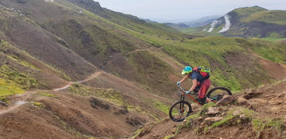 Person on mountain bike riding through grassy hills in Iceland