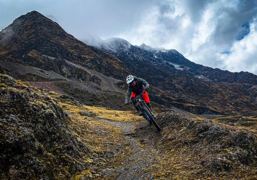 A rider biking coming down a mountain trail in Peru.