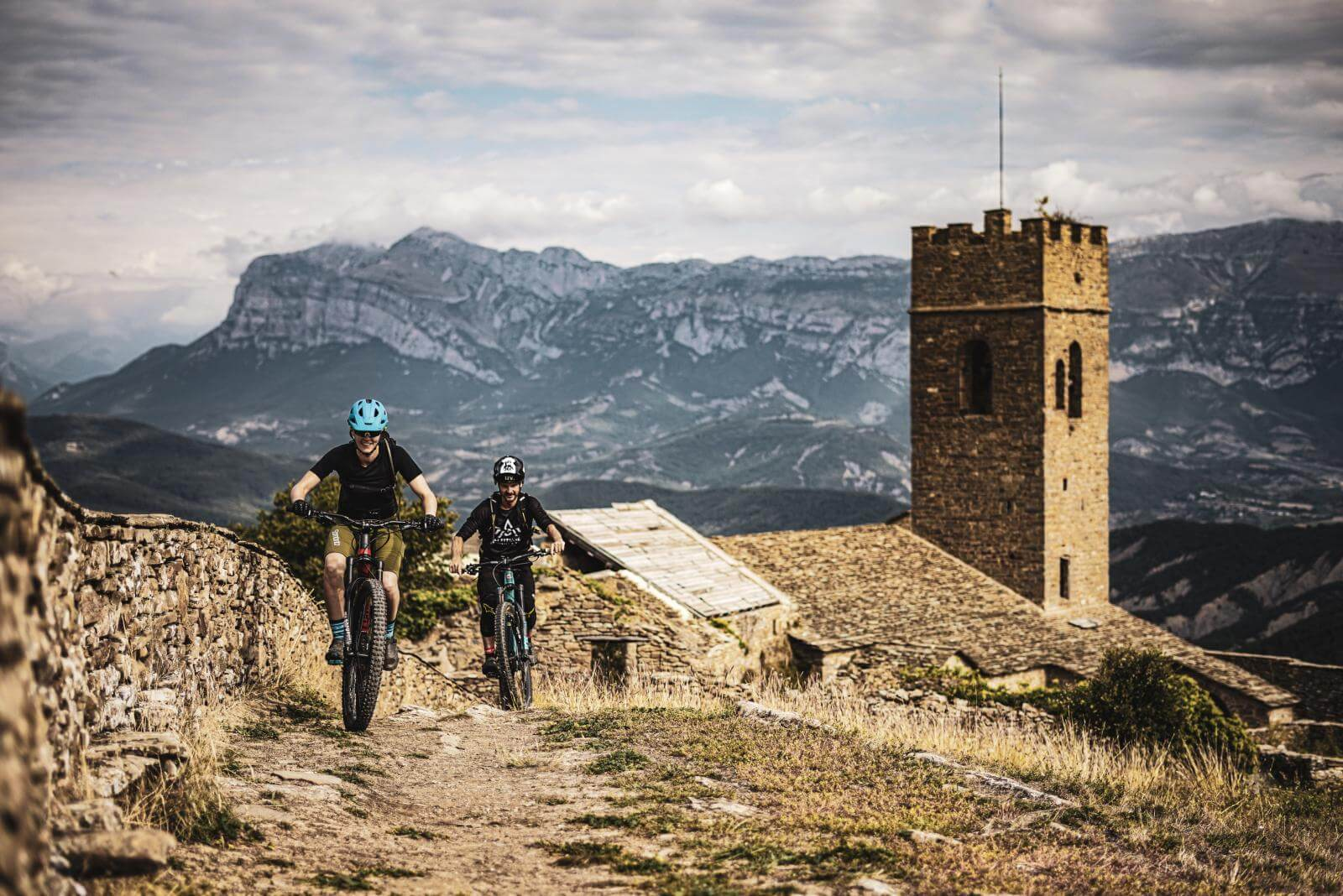 Two mountain bikers riding through Spain, coming up over a hill on a brown dirt path with the Pyrenees and an old stone fortress behind them.