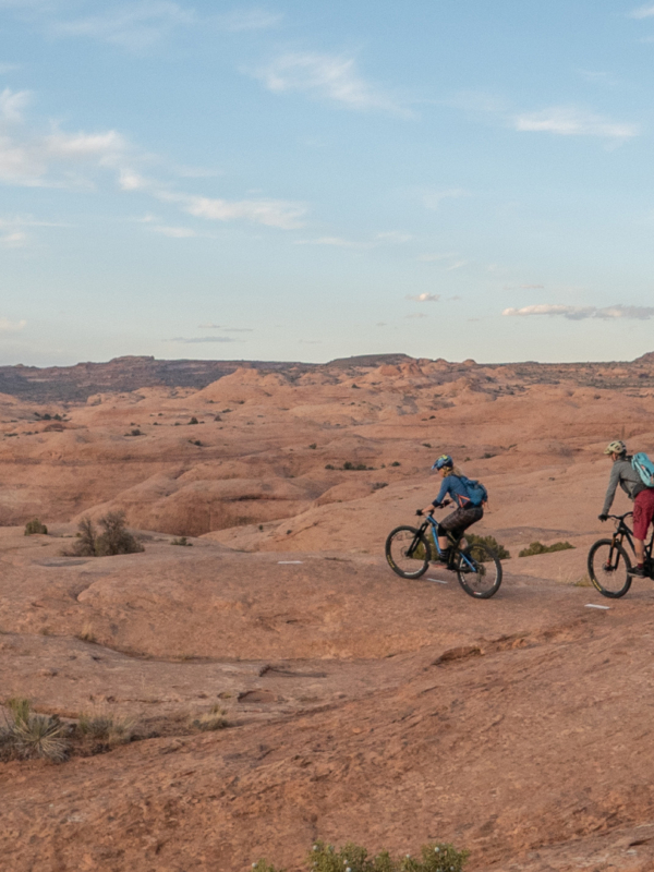 Three people on bikes riding across Moab Desert