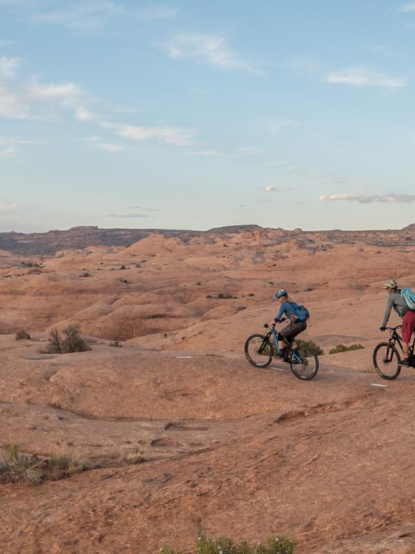 Three people on bikes riding across Moab Desert