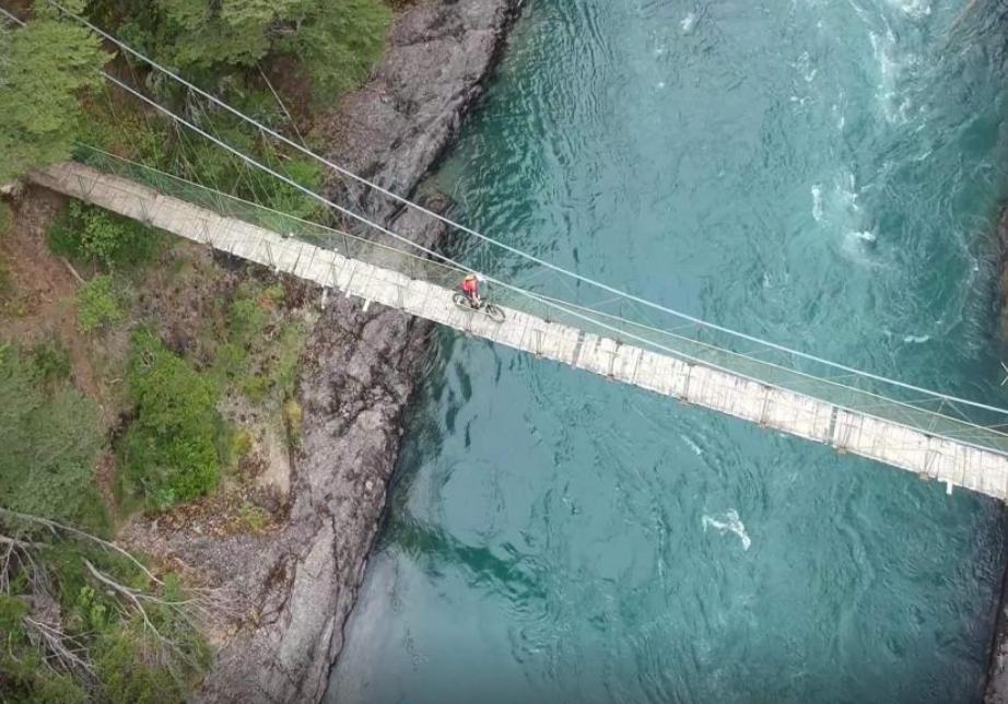 Mountain Biker walking bike over a small, wood suspension bridge over wide blue river