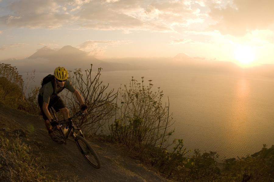 Person on mountain bike riding towards camera from the left with sun setting over mountains in distance