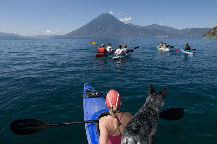 Several people in Kayaks with mountain peak in distance