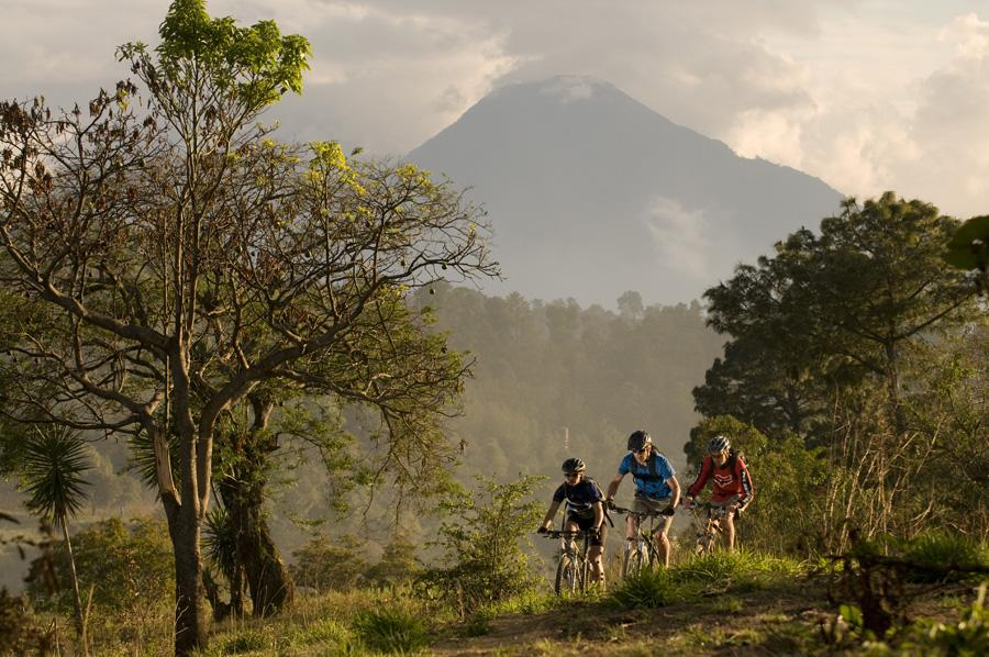 Three mountain bikers riding towards the camera with volcano peak in distance in Guatemala