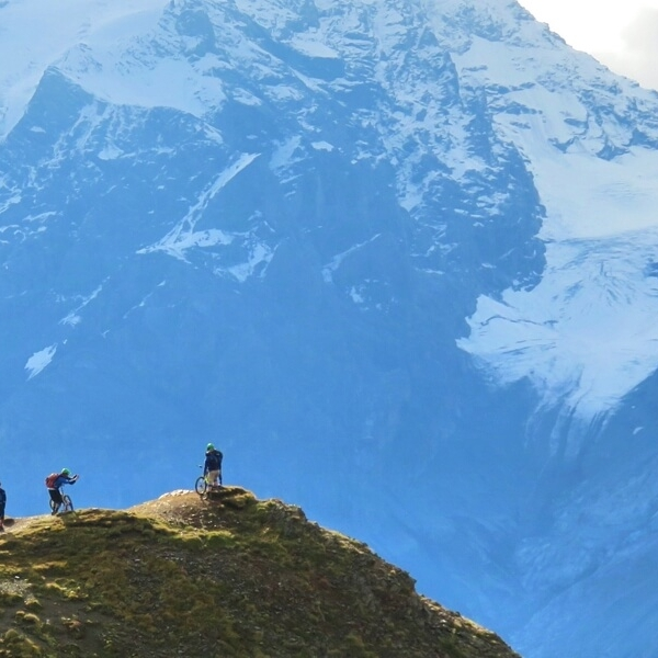 Riders standing with their bikes on a tall hill as they look across to snow-covered Alps