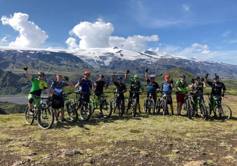 Many mountain bikers standing in a line to pose for picture while standing on grassy area in Iceland