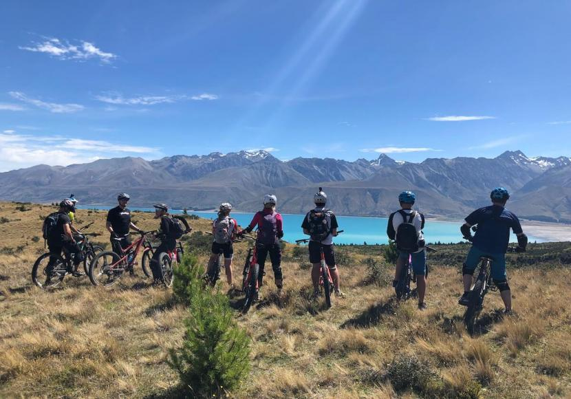 Group of mountain bikers standing next to there bikes as they look out over a lake and New Zealand landscape