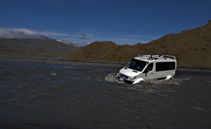 White tour van driving across field of water that's over a foot deep